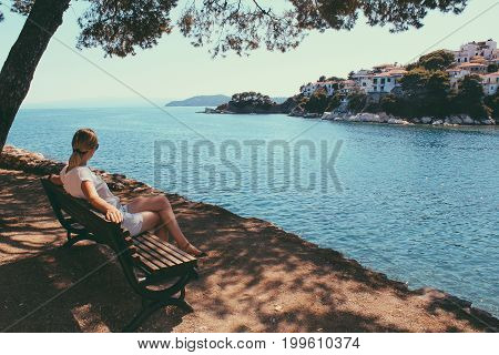 Female Traveler Admiring A Marine View. Side View Of Woman Traveler, Sitting With The Arms Along The