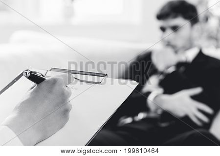 Over the shoulder view, of a business man sit on a couch talking to his psychiatrist