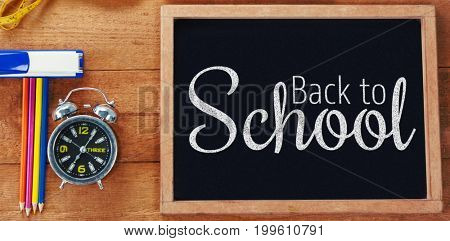 Digital image of back to school text against overhead view of chalkboard with equipment
