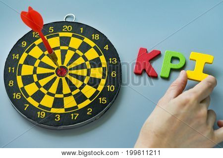 Female hand holding colorful wooden alphabet KPI with dartboard as KPI Goals or Target concept.