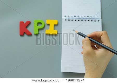Selective focus on hand holding pencil on white paper note and colorful wooden alphabet KPI.