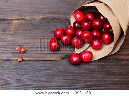 Red cherry in a paper bag on a brown wooden background