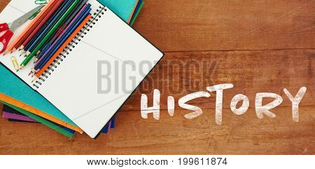 History text against white background against overhead view of books and pencils