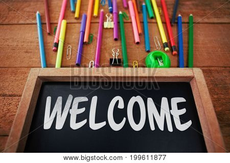 Welcome text against white background against chalkboard with colorful pencils on table