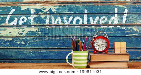 Get involved text against white background against books with alarm clock on table