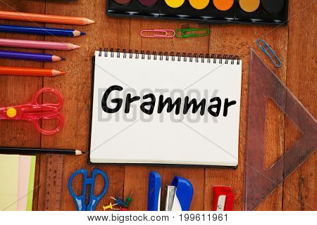 Grammer text on white background against overhead view of school supplies on table