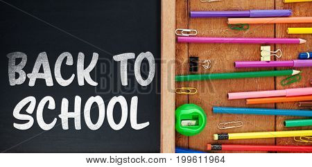 Back to school text on white background against multi colored pencils with chalkboard
