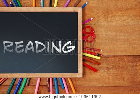 Reading text against white background against high angle view of chalkboard with multi colored equipment