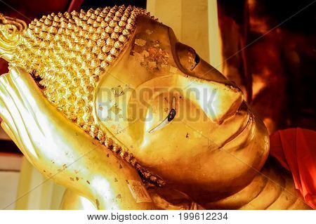 Head of golden reclining Buddha Image stuck with gold leaf on the face
