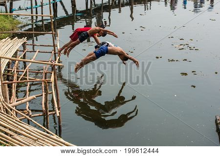 Mahasarakham Thailand - February 22 2016: Rural children lifestyle having fun by jumping into river together in Mahasarakham Thailand.