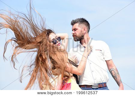 Sexy girl and guy with tender face expressions hug each other. Shopping and love concept. Man with beard and woman with messy long hair hold shopping bags. Couple carries packets on blue background