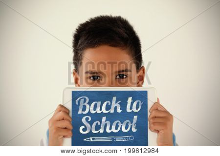Back to school text over white background against schoolboy holding digital tablet against white background