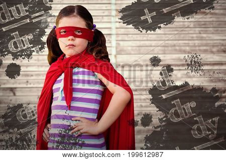 Portrait of girl standing in superhero costume against digitally generated grey wooden planks