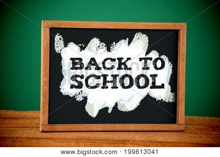 Back to school text on green and blue splash against empty blackboard on wooden table