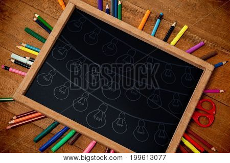 Graphic image of light bulbs arranged against high angle view of chalkboard with colorful equipment