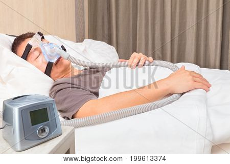 middle age asian man sleeping in his bed wearing CPAP mask connecting to air hose and CPAP machine device for people with sleep apnea