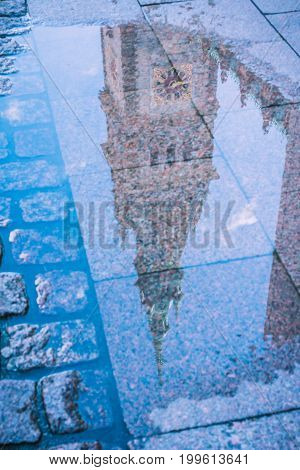 Reflection of City Hall Tower in a puddle. Hamburg, Germany.