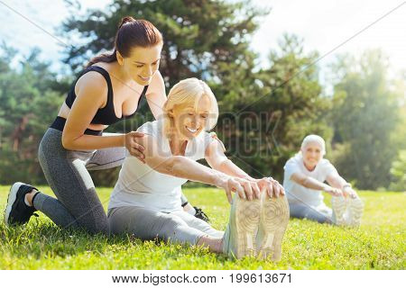 Supporting you. Positive senior female sitting on the grass in semi position and keeping eyes closed while smiling during process