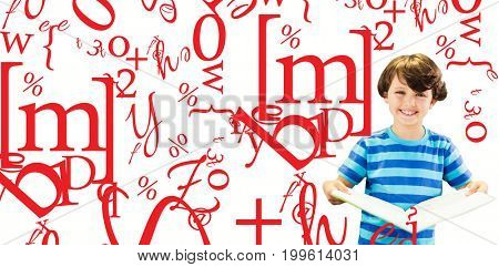 Portrait of smiling boy holding book against letter and number jumble