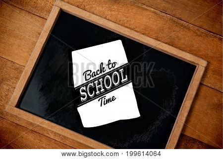 Graphic image of back to school text on paper against tilt chalkboard on wooden table