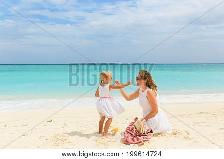mother and daugghter applying sunblock cream on tropical beach