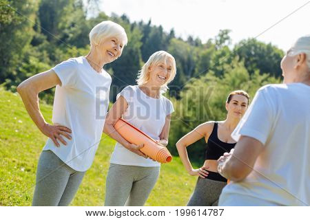Emotional women. Cheerful blonde standing in semi position and keeping smile on face while putting hands on the waist
