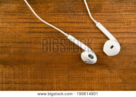 White Little Headphones On A Wooden Isolated Background. Horizontal Frame