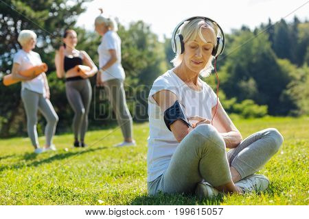 Searching song. Positive mature female crossing legs while sitting on the grass and using her telephone