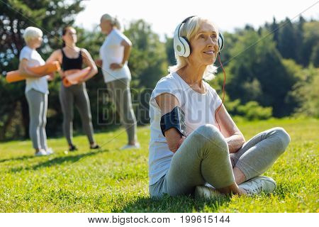 Moment of relaxation. Delighted woman keeping smile on face and wearing headphones while enjoying music