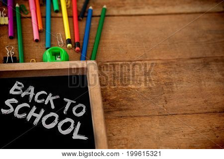 Graphic image of red back to school text against chalkboard with colored pencils on table