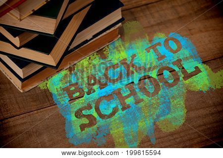 Back to school text on green and blue splash against high angle view of books on table