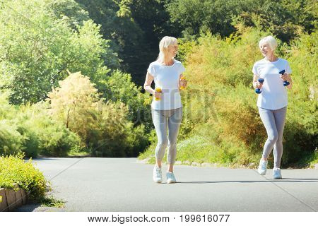 Friendly talk. Happy senior woman holding dumbbells in both hands and keeping smile on face while jogging