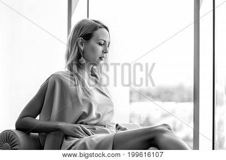 Beautiful luxury woman sitting on sofa near window and wearing pink fashion dress