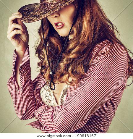 Beautiful cowgirl style woman wearing cowboy hat studio shot