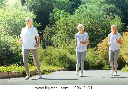 Lets run. Positive delighted women wearing comfortable clothes and keeping smile on faces while enjoying sport activities