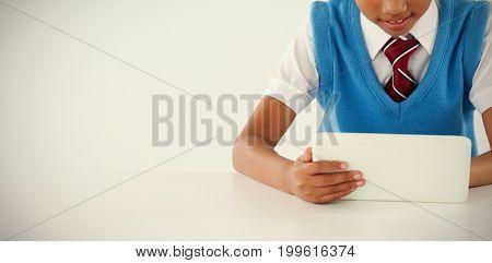 Schoolboy using digital tablet against white background