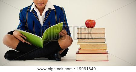 Portrait of schoolboy studying against white background