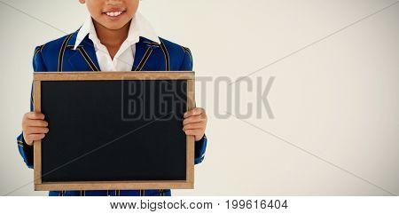Portrait of schoolboy holding blank writing slate against white background