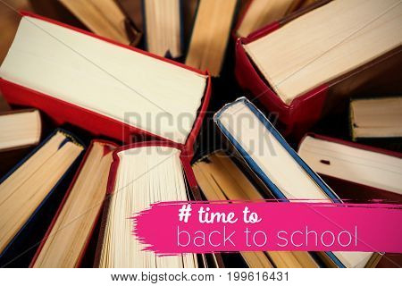 Back to school text with hashtag  against close-up of books arranged