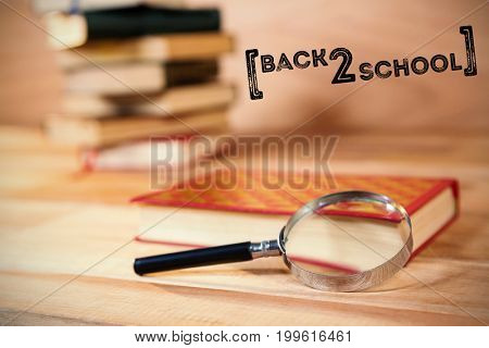 Back to school text over white background against magnifying glass with book on table