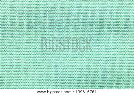 Light green background from a textile material with wicker pattern closeup. Structure of the pastel turquoise fabric with natural texture. Cloth backdrop.