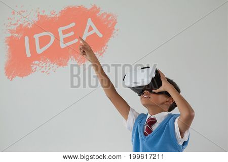 Digital composite image of idea text on black spray paint against schoolboy using virtual reality headset