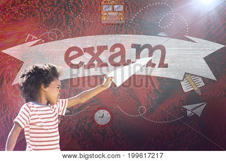 Playful boy playing with paper airplane against exam against black background