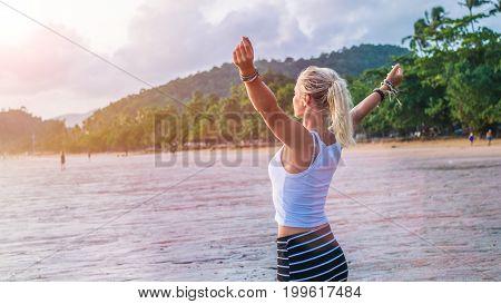 Happy blond beautiful women raising her hands on Ao Nang beach at sunset, Krabi Thailand.
