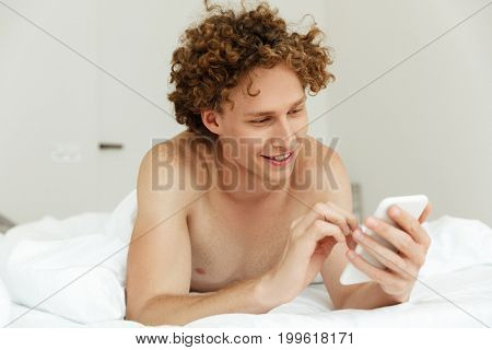 Handsome young man typing a message on mobile phone while lying in bed at home