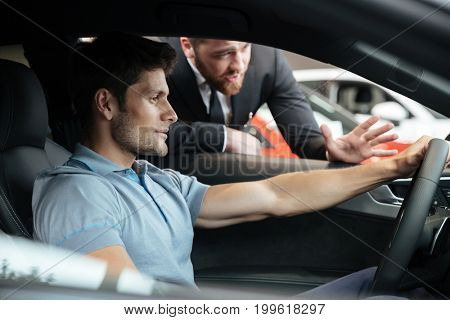 Professional young male dealer selling car to a customer at the dealership