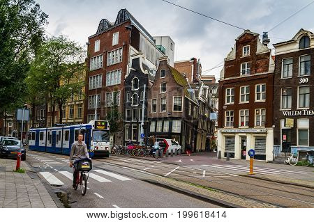 AMSTERDAM NETHERLANDS - JULY 27 2017: Unknown person riding a bicycle with a tram on a background. Asterdam with historic houses and channels popular among tourists.