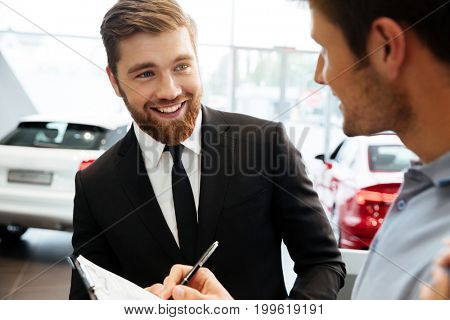 Smiling young dealer selling new car to a male customer and filling documents
