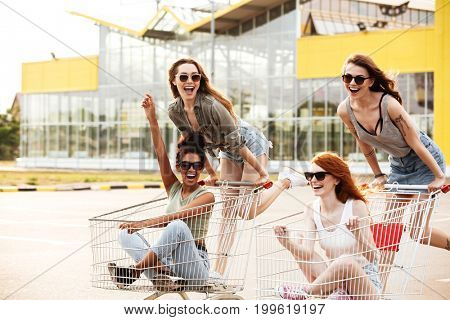 Four crazy laughing girls in sunglasses having fun shopping trolley race outdoors