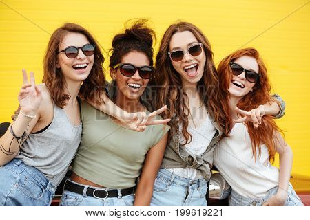 Image of four young happy women friends standing over yellow wall. Looking at camera.